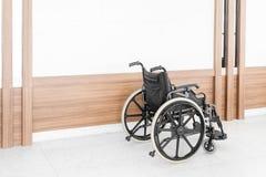 Lege die rolstoel in het ziekenhuisgang wordt geparkeerd stock afbeeldingen