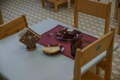 Lege die schotels voor ontbijt in kleuterschool worden geplaatst Kleuterschool binnenmening Stoelen en lijsten meubilair stock afbeelding