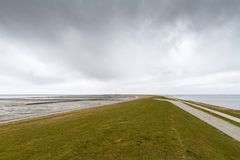 Lege dijk met bewolkte hemel dichtbij Nordstrand, Sleeswijk-Holstein stock afbeelding