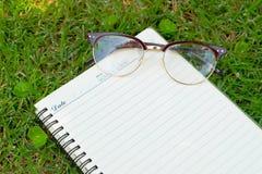 Lege document en glazen op groen gras Stock Afbeeldingen