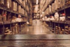 Lege donkere houten lijstbovenkant op vaag pakhuis royalty-vrije stock foto's