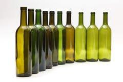 Lege flessen die zich op een rij op witte achtergrond bevinden Royalty-vrije Stock Foto's
