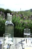 Lege flessen en glazen op houten lijst Stock Fotografie