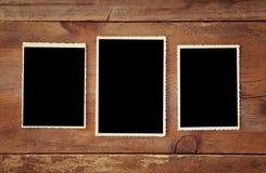 Lege fotoframes op houten achtergrond Stock Afbeeldingen