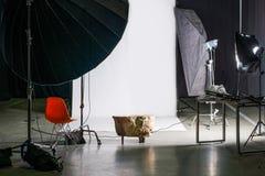 Lege fotostudio met modern binnenland en verlichtingsmateriaal Voorbereiding voor studio die schieten: lege stoel en studioverlic Royalty-vrije Stock Afbeeldingen