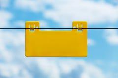 Lege gele die informatieplaat op een elektroomheining tegen blauwe hemel wordt gehangen Stock Foto's