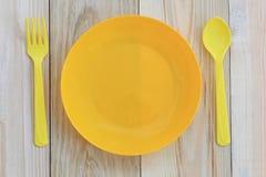 Lege gele plastic die schotel en lepel op houten vloer wordt geplaatst Royalty-vrije Stock Foto's