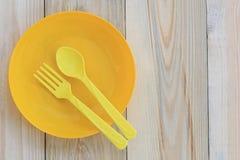 Lege gele plastic die schotel en lepel op houten vloer wordt geplaatst Stock Foto