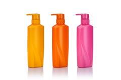Lege gele, roze en oranje plastic die pompfles voor shamp wordt gebruikt Stock Fotografie
