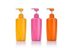 Lege gele, roze en oranje plastic die pompfles voor shamp wordt gebruikt Stock Afbeeldingen