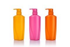 Lege gele, roze en oranje plastic die pompfles voor shamp wordt gebruikt Royalty-vrije Stock Afbeeldingen