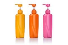Lege gele, roze en oranje plastic die pompfles voor shamp wordt gebruikt Stock Foto