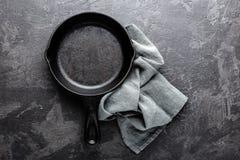 Lege gietijzerpan op donkere grijze culinaire achtergrond, mening van hierboven Stock Fotografie