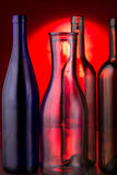 Lege glasflessen op rode achtergrond Stock Fotografie