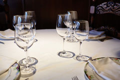 Lege glazen in een restaurant op wit tafelkleed Schaduw, bruine achtergrond en gesneden stoelen Stock Afbeeldingen