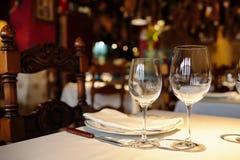 Lege glazen in een restaurant op wit tafelkleed Schaduw, bruine achtergrond en gesneden stoelen Royalty-vrije Stock Afbeeldingen