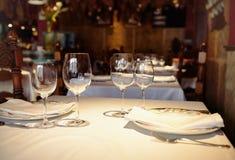 Lege glazen in een restaurant op wit tafelkleed Schaduw, bruine achtergrond en gesneden stoelen Stock Foto's