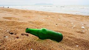 Lege groene bierfles op het strand stock foto