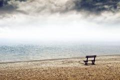 Lege houten bank op het strand in bewolkt weer Stock Foto's