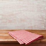 Lege houten deklijst met rood gecontroleerd tafelkleed over rustieke muurachtergrond voor de vertoning van de productmontering stock afbeeldingen