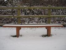 Lege houten die autobank volkomen met witte sneeuw wordt behandeld Stock Fotografie