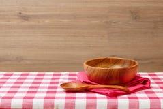 Lege houten kom en lepel op een rood geruit tafelkleed Houten achtergrond Stock Foto