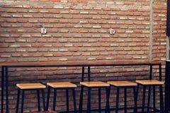 Lege houten lijst en stoelen voor straatvoedsel, bakstenen muurtekst Stock Afbeeldingen