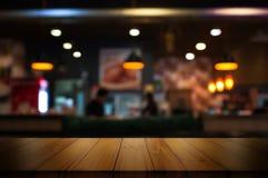 Lege houten lijstbovenkant met de winkel van de onduidelijk beeldkoffie of restaurant inter Royalty-vrije Stock Afbeeldingen