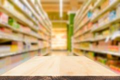 Lege houten lijstbovenkant of plank met de vage achtergrond van winkelplanken stock fotografie