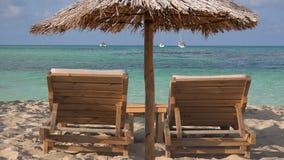 Lege houten zitkamer twee sunbeds en grote rietparaplu op tropisch exotisch strand stock videobeelden