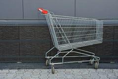 Lege ijzerkar van de supermarkt dichtbij de muur royalty-vrije stock foto's