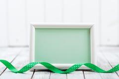 Lege kaart met groen lint op witte houten achtergrond Stock Afbeeldingen