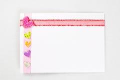 Lege kaart met kleurrijke harten over roze lint Royalty-vrije Stock Afbeelding