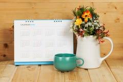 Lege kalender met kop en vaas op hout Royalty-vrije Stock Foto's