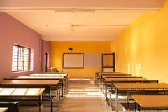 Lege klassenruimte en bureaus met kleurrijke muren royalty-vrije stock fotografie