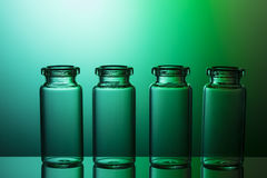 Lege kleine flessen op aardige blauwgroene gradiëntachtergrond stock fotografie