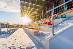 Lege Kleurrijke Voetbal ( Soccer) Stadionzetels in de Winter in Sneeuw - Sunny Winter Day met Zongloed die wordt behandeld stock foto's