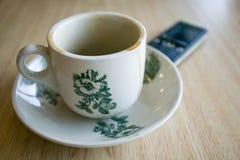 Lege koffiekop en telefoon Stock Afbeeldingen