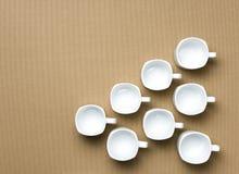 Lege koffiekoppen op lichtbruine achtergrond Royalty-vrije Stock Afbeeldingen