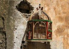 Lege kooi voor vogels op een oude, verbrijzelde muur Stock Foto's
