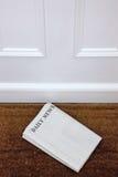 Lege krant die op een deurmat ligt. stock afbeeldingen