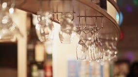 Lege kristalglazen die in de bar hangen stock video
