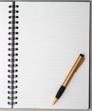 Lege lege ring, spiraalvormige blocnote, één gouden pen Royalty-vrije Stock Foto
