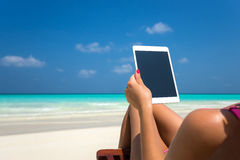Lege lege tabletcomputer in de handen van vrouwen op het strand Stock Foto