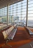 Lege leunstoelen in zaal van verwachting van luchthaven en vliegtuig achter venster Royalty-vrije Stock Foto's