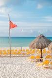 Lege ligstoelen in de ochtend op een strand onder palmbladparaplu met rode vlag (Mexico, Mei 2015) Stock Afbeeldingen