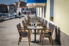 Lege lijsten en stoelen van een koffie in Cres Royalty-vrije Stock Fotografie