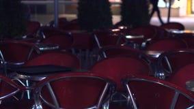 Lege lijsten en stoelen van een straatkoffie bij nacht stock video