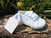 Lege markering op kleine babyschoen met bloemen/zwangerschapsaankondiging Stock Foto's