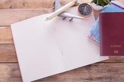 Lege notitieboekje, paspoort, kompas, vliegtuig en kaart op houten lijst stock fotografie